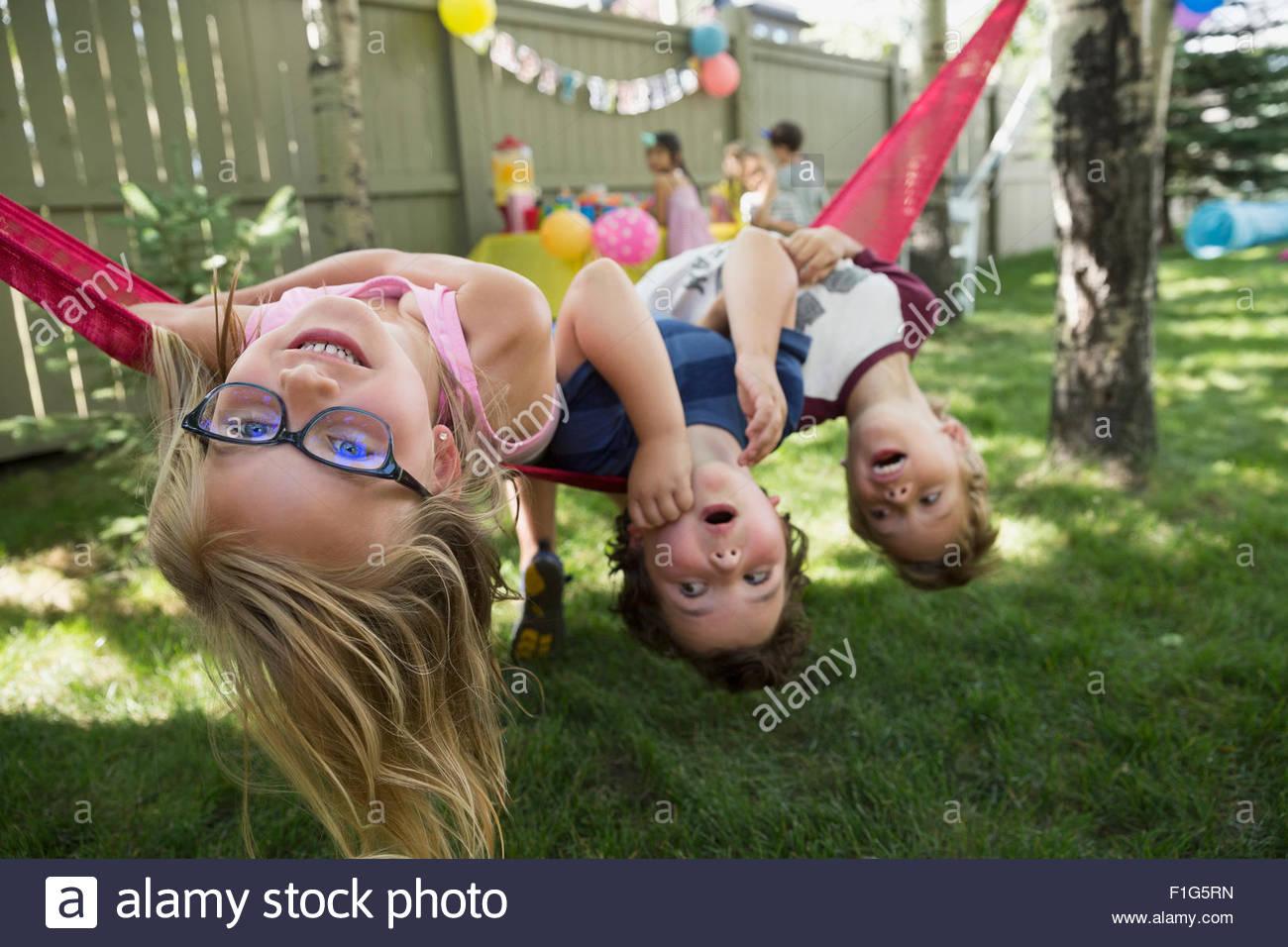 Portrait upside-down kids hammock backyard birthday party ...