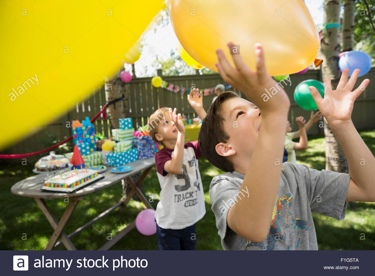 boys playing with balloons at backyard birthday party stock photo