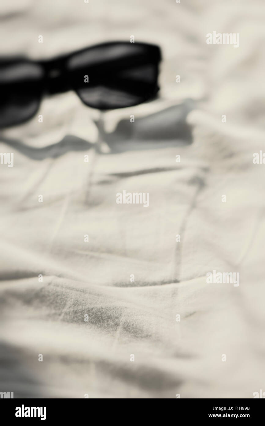 Rumpled bed sheet - Empty Bed With Crumpled Bed Sheet And A Pair Of Sunglasses