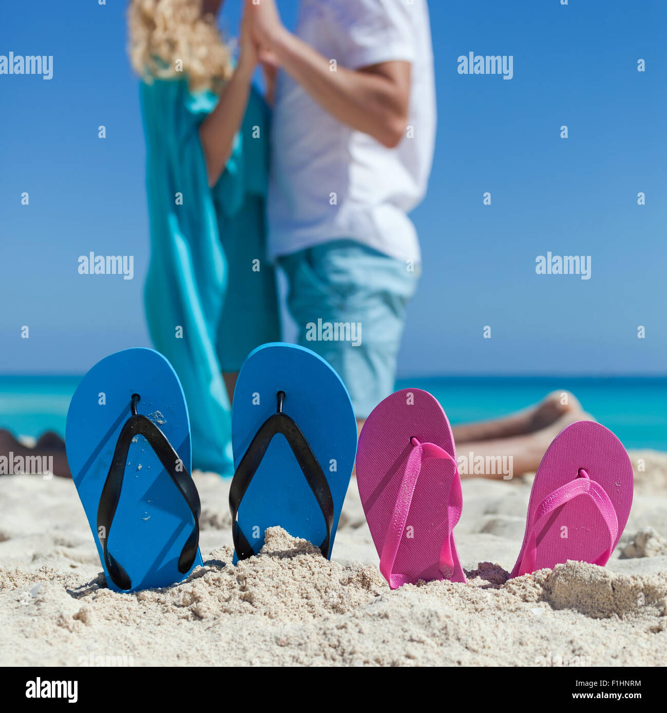 Happy Couple Sitting On Sandy Beach Embracing Kissing: Pair Of Color Flip Flops On Sandy Beach Near Sea With