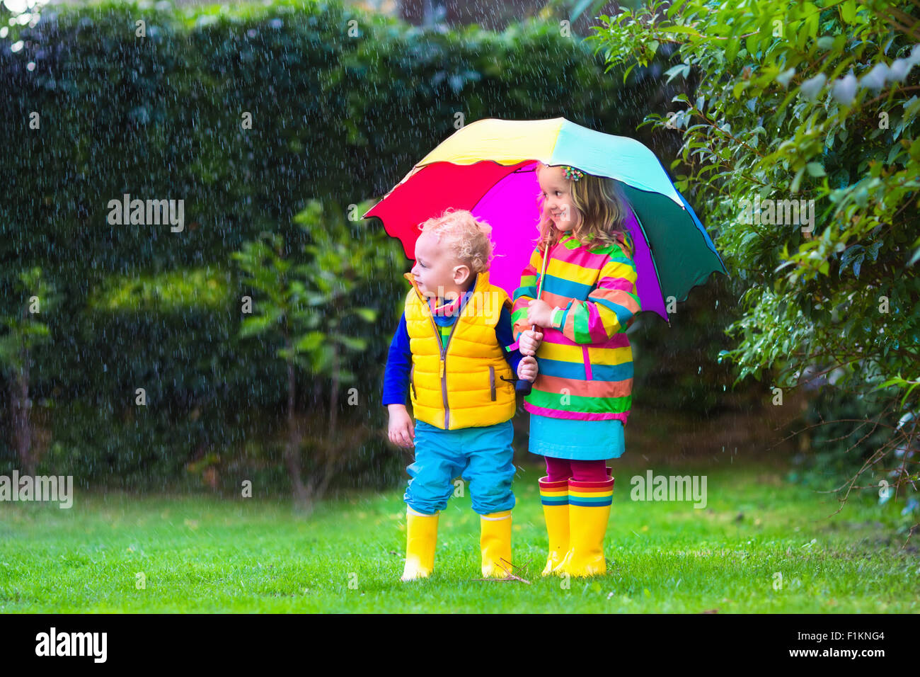 little and boy with colorful umbrella playing in the rain