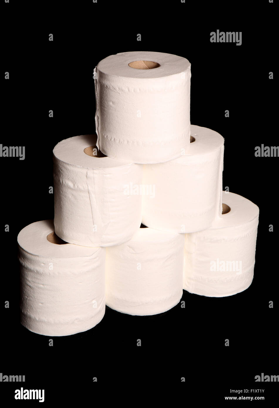 stack of toilet paper rolls on black background stock