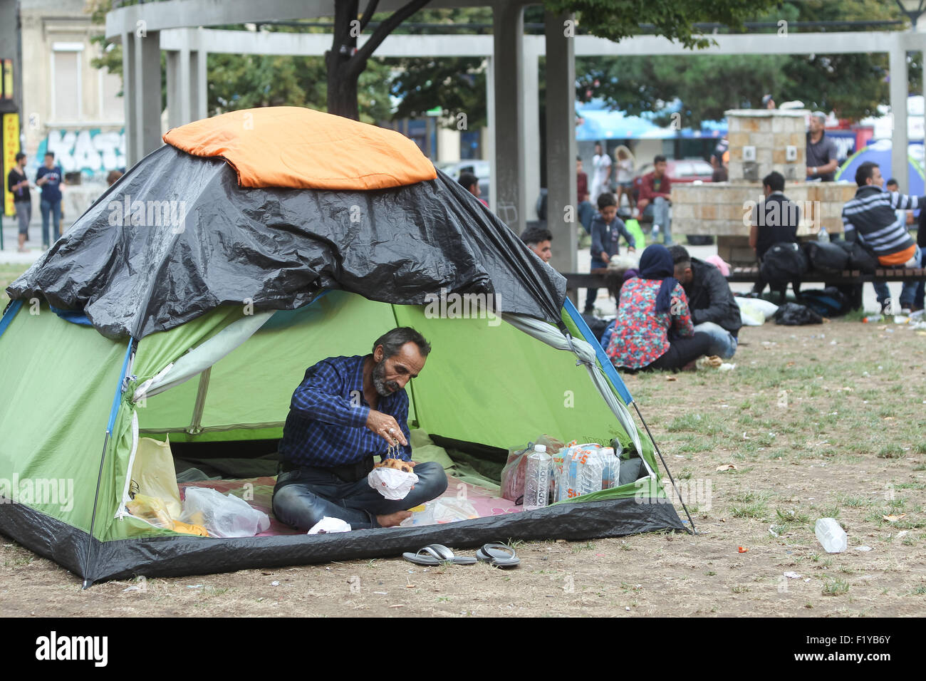 A syrian refugee resting in a tent and eating while waiting for the transport to the European Union in Belgrade Serbia & A syrian refugee resting in a tent and eating while waiting for ...