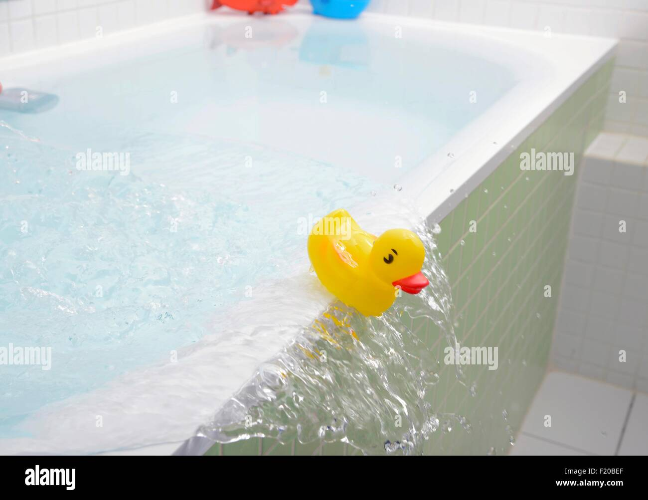 rubber duck falling out of bath overflowing with water stock photo