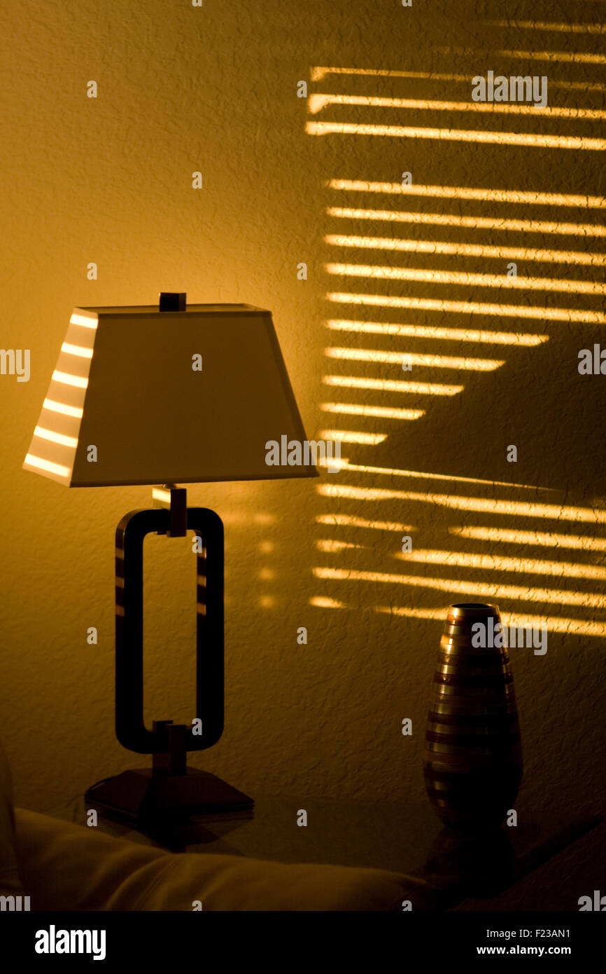 Dark room with light through window - Bright Sunshine In A Dark Room Casts Lines Through Window Blinds And On To A Lamp