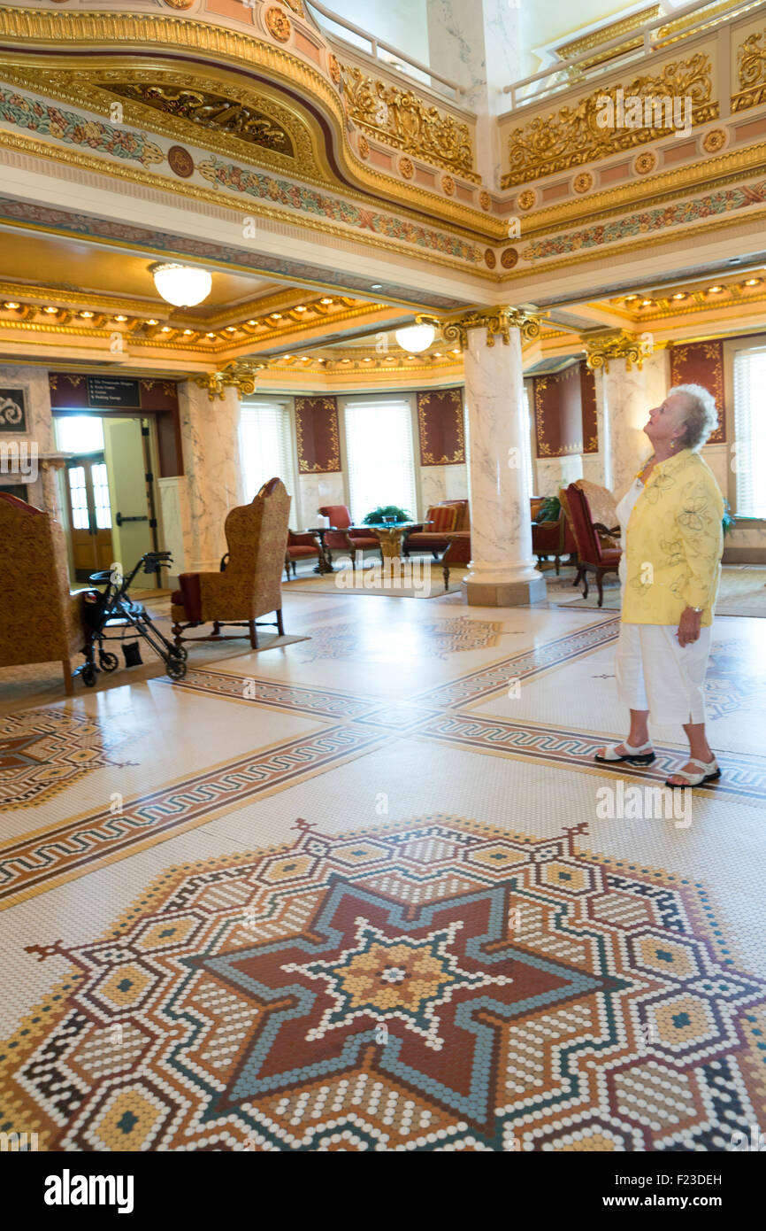 senior woman standing near mosaic tile floor looking up at gold
