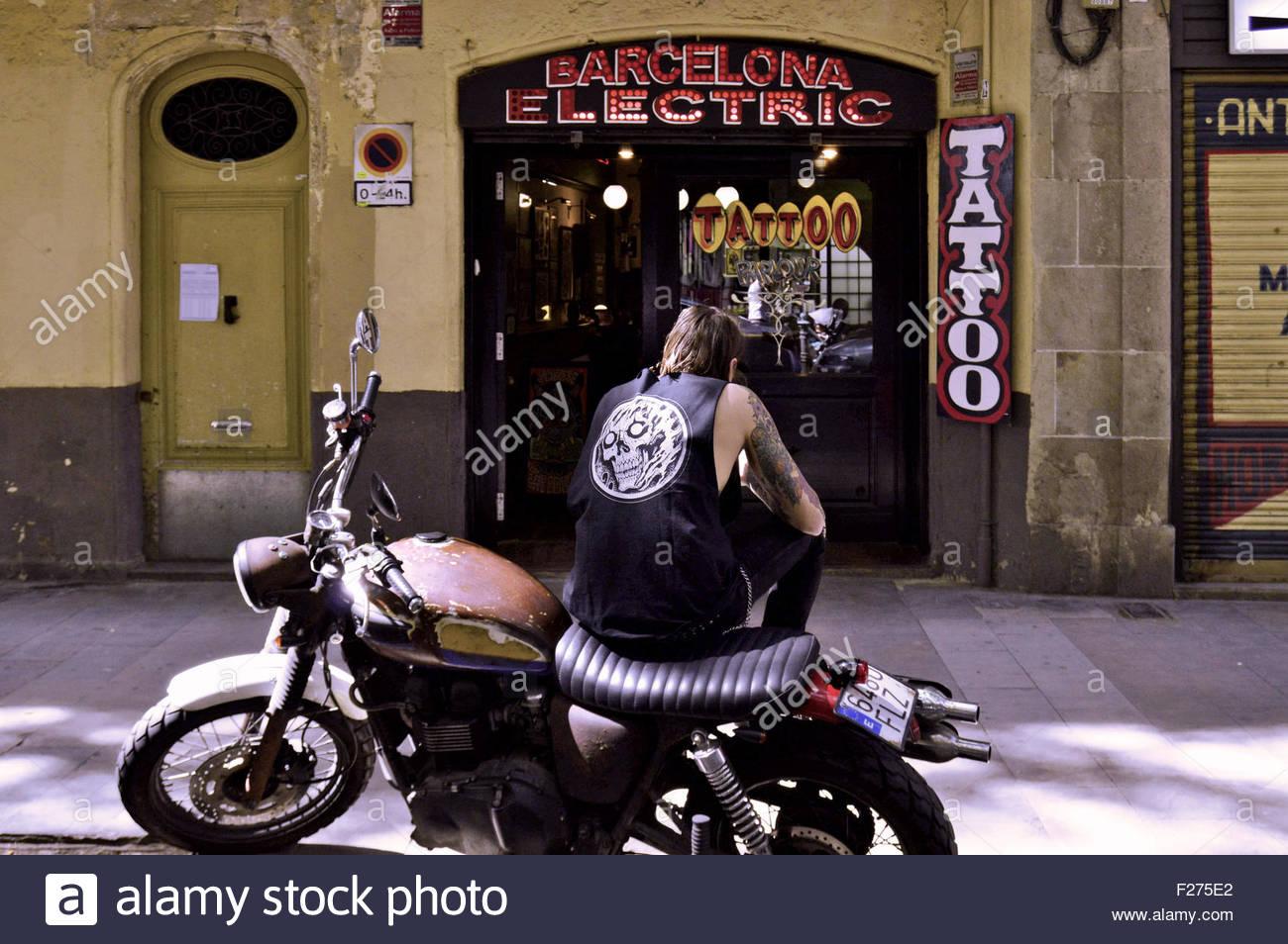 Motorcycle with biker tattoo - Man Biker Sitting On Motorcycle Outside Tattoo Parlour In Ciutat Vella Barcelona Catalonia Spain Europe