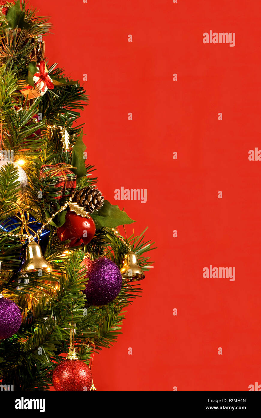 Christmas Tree With Lights And Ornaments On Red Background Vertical