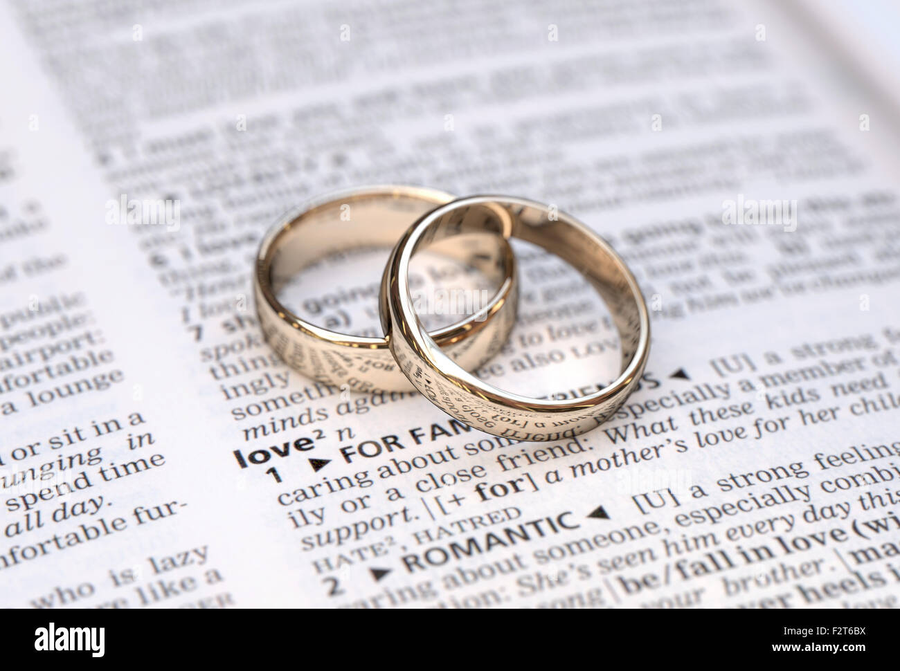 Wedding rings on a dictionary page showing love definition close up