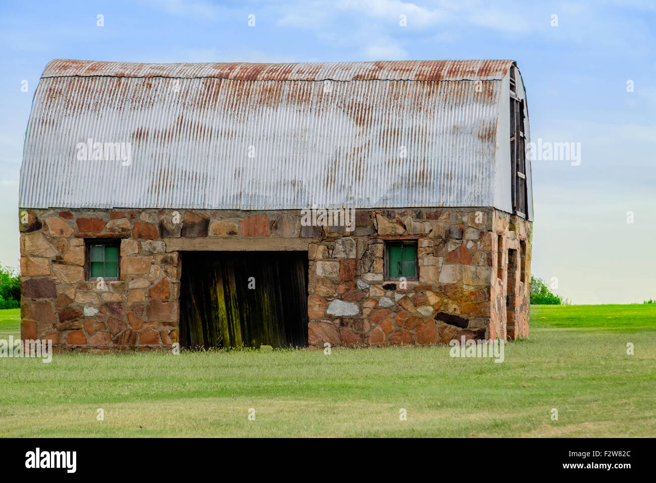 An Old Rustic Stone Barn With A Rusty Tin Roof In The Oklahoma, USA  Countryside.