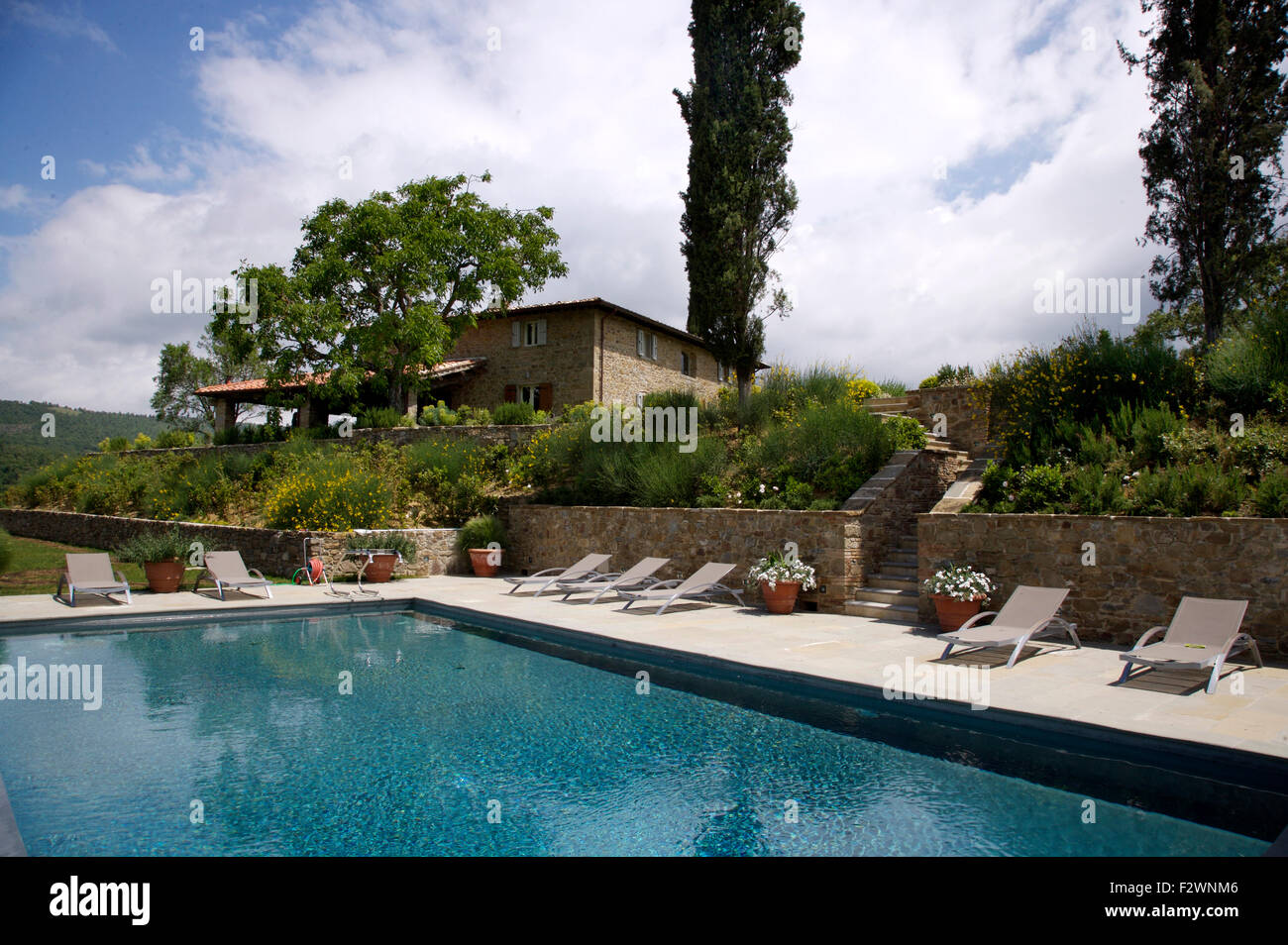 Loungers beside swimming pool in large italian country garden stock photo royalty free image for Large swimming pools for gardens