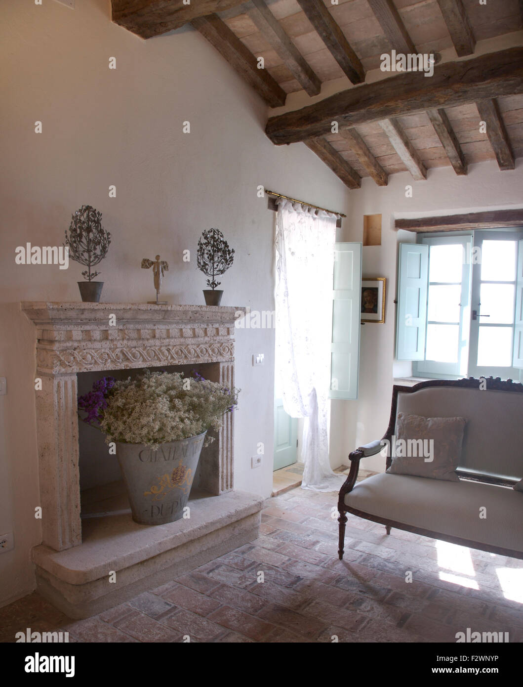 Bedroom stone fireplace - Dried Flowers In Galvanised Zinc Bucket In Ornate Stone Fireplace In Italian Country Bedroom With An Antique Sofa