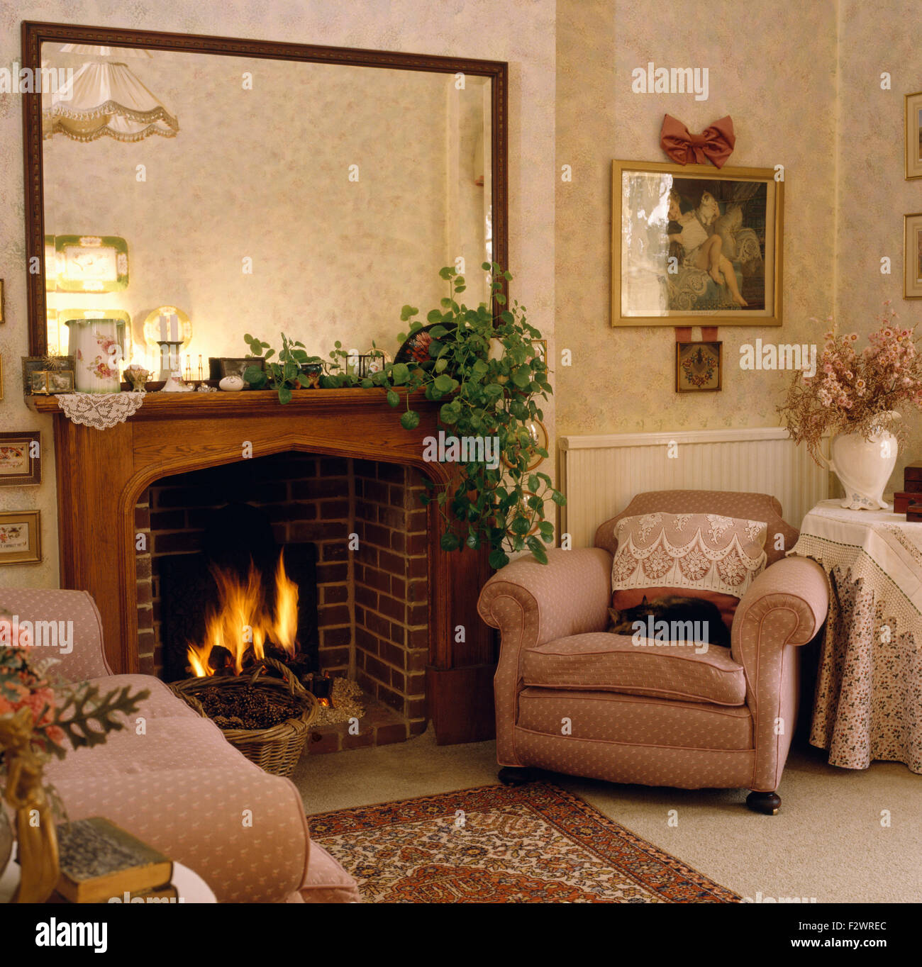 Large mirror above fireplace with lighted fire in eighties living ...