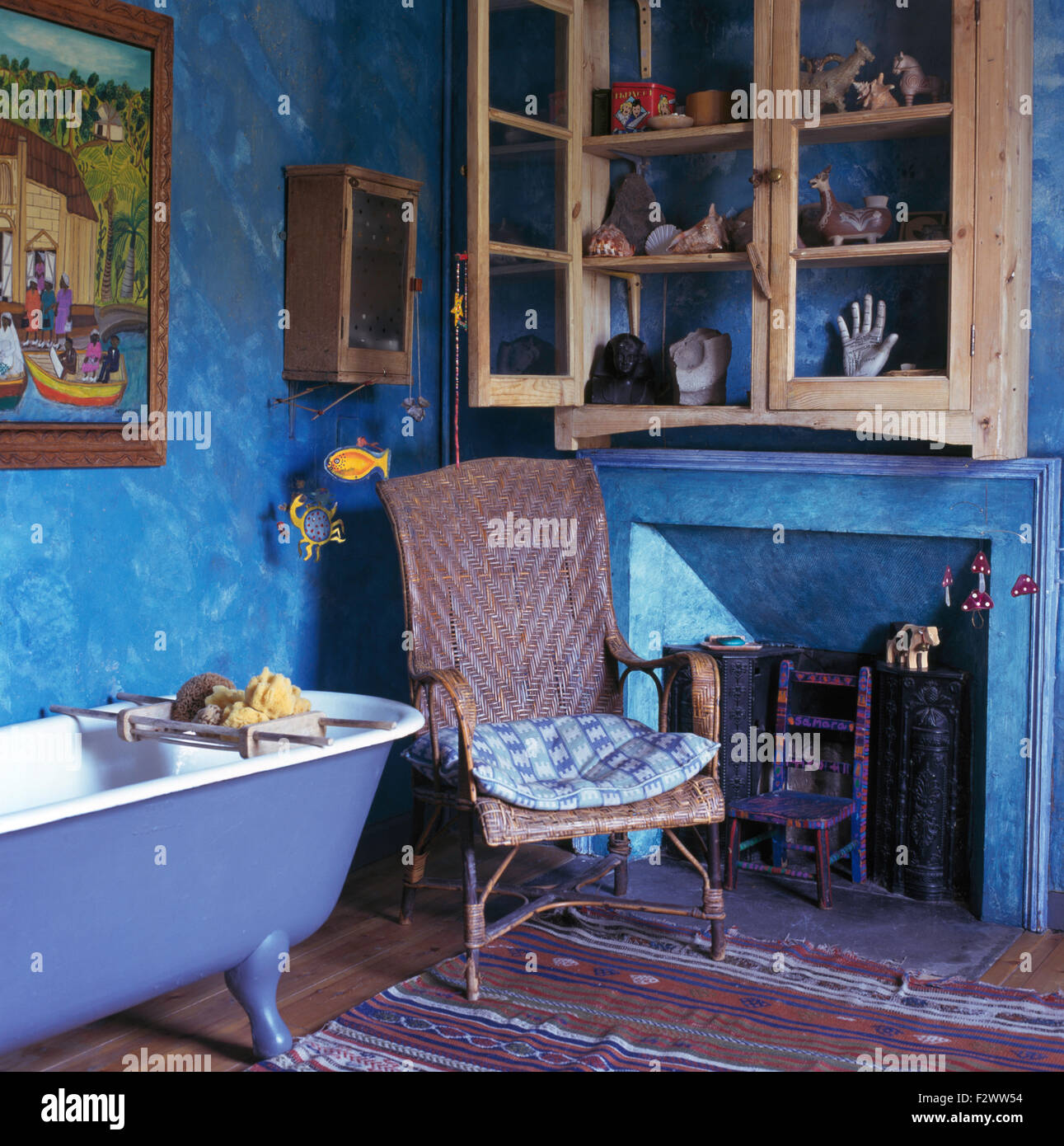 glass front wall cupboard above fireplace and cane chair in blue