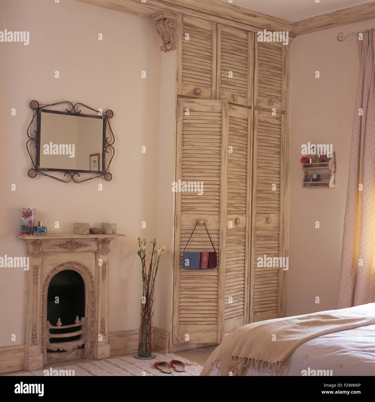 Mirror Above Small Painted Fireplace In Townhouse Bedroom