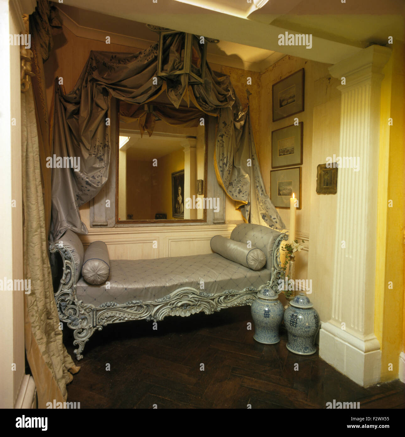 Grey silk drapes and mirror above upholstered baroque bed for Baroque style bed