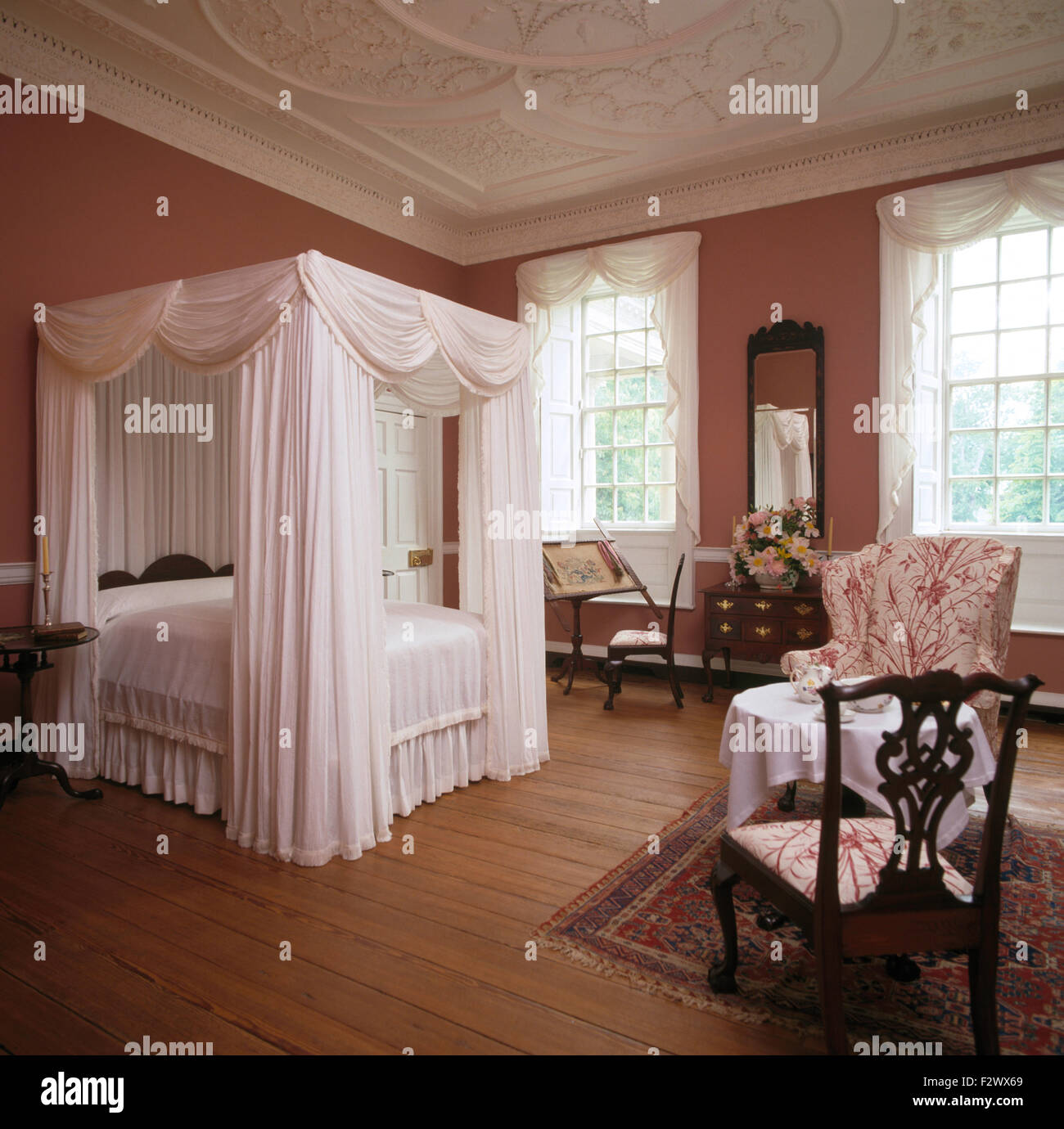 Bedroom ceiling drapes -  White Drapes And Linen On Four Poster Bed In Elegant Colonial Style Bedroom With Wooden Flooring