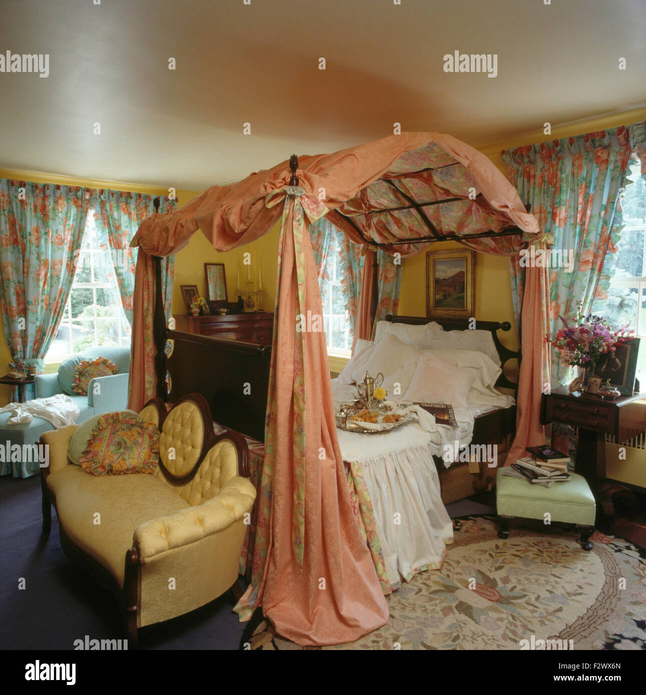Small yellow sofa at the foot of a four poster bed with for Small four poster bed