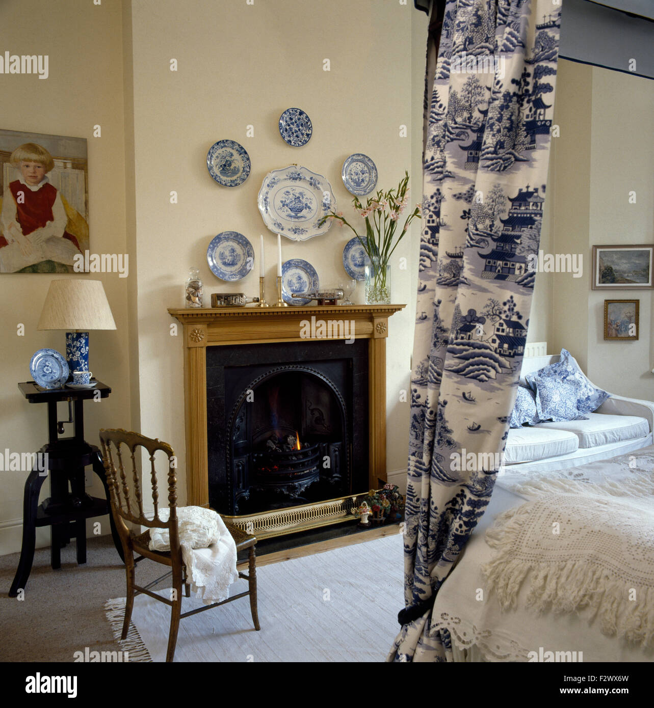 Collection of blue+white plates on wall above fireplace in bedroom ...