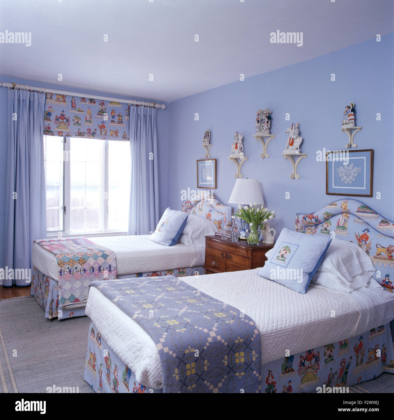 Welsh Blanket And A Patchwork Quilt On Single Beds In Pale Blue Bedroom  With Blue Drapes And Patterned Blind