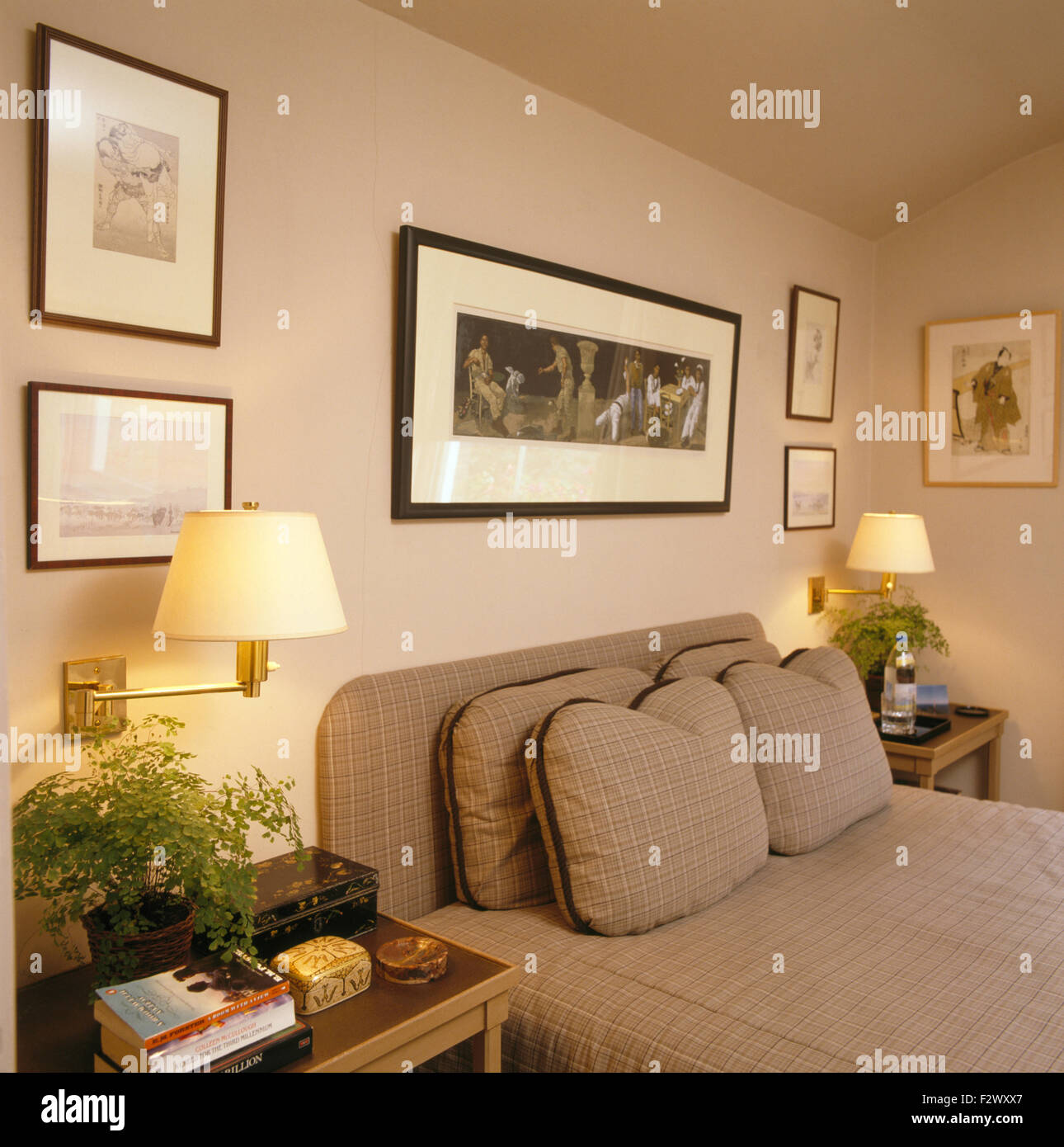 Lighted wall lamps on either side of bed with fitted cover and cushions in  nineties bedroom. Lighted wall lamps on either side of bed with fitted cover and
