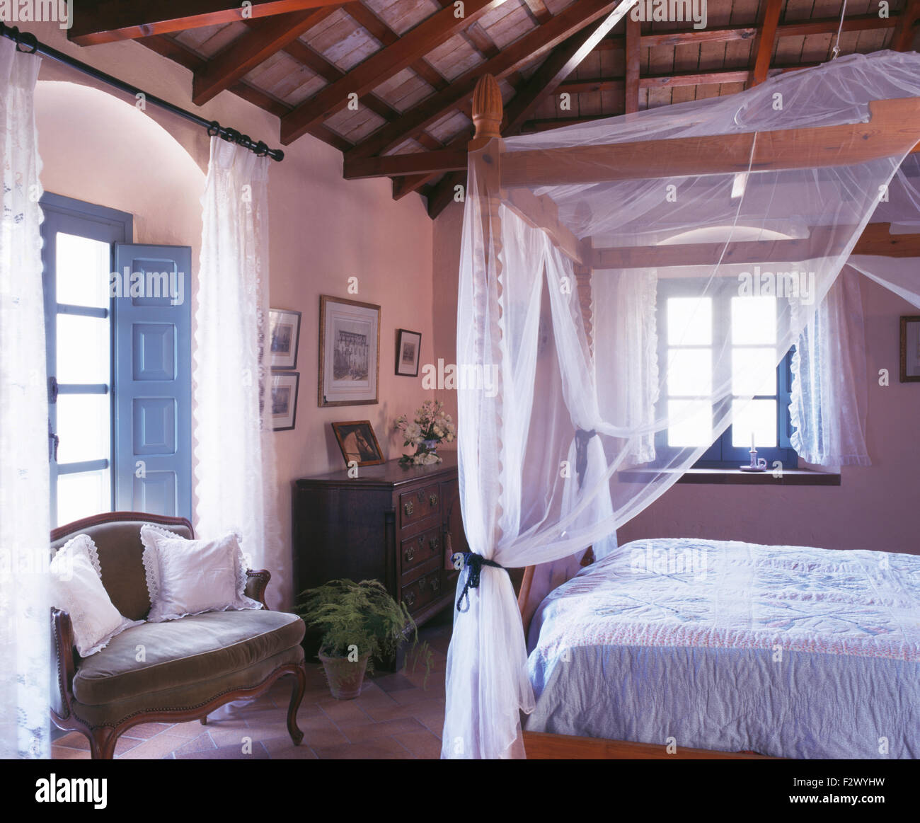 four poster bed with white mosquito net in rustic spanish country