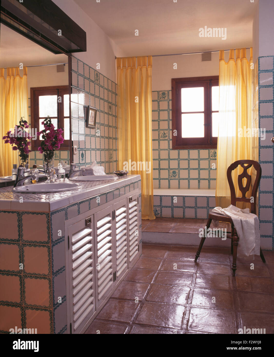 Yellow shower curtains on bath in tiled Spanish country bathroom ...