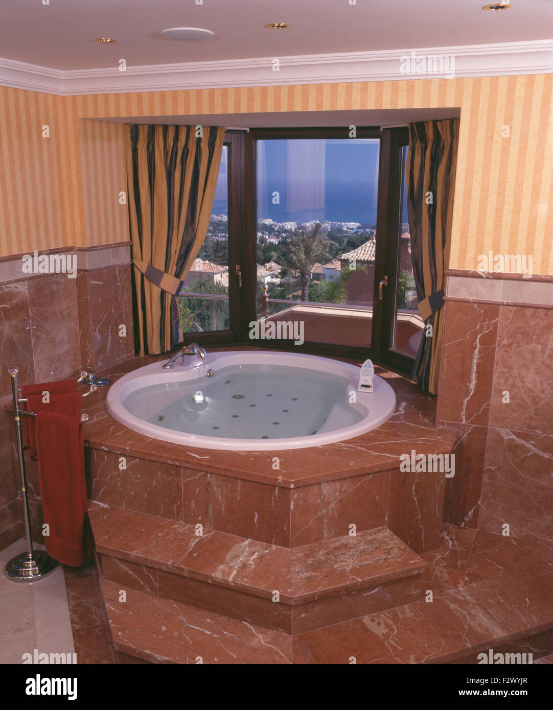 spanish villa bathroom with brown marble steps up to jacuzzi bath