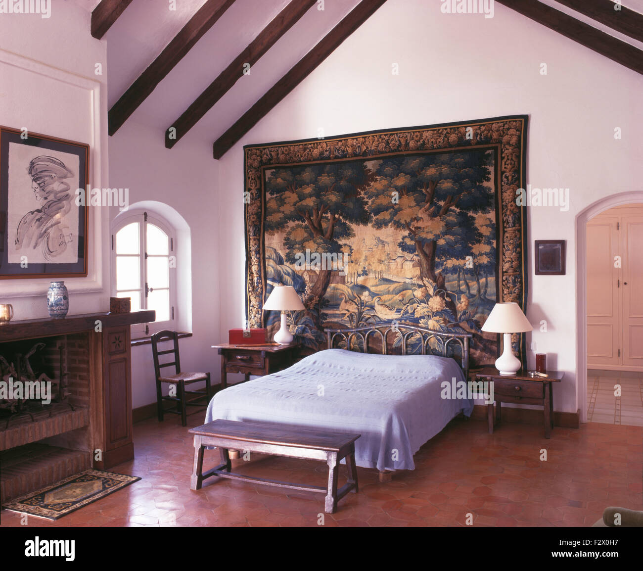 bedroom tapestry. Large antique tapestry behind bed in white Spanish country bedroom with a  terracotta tiled floor