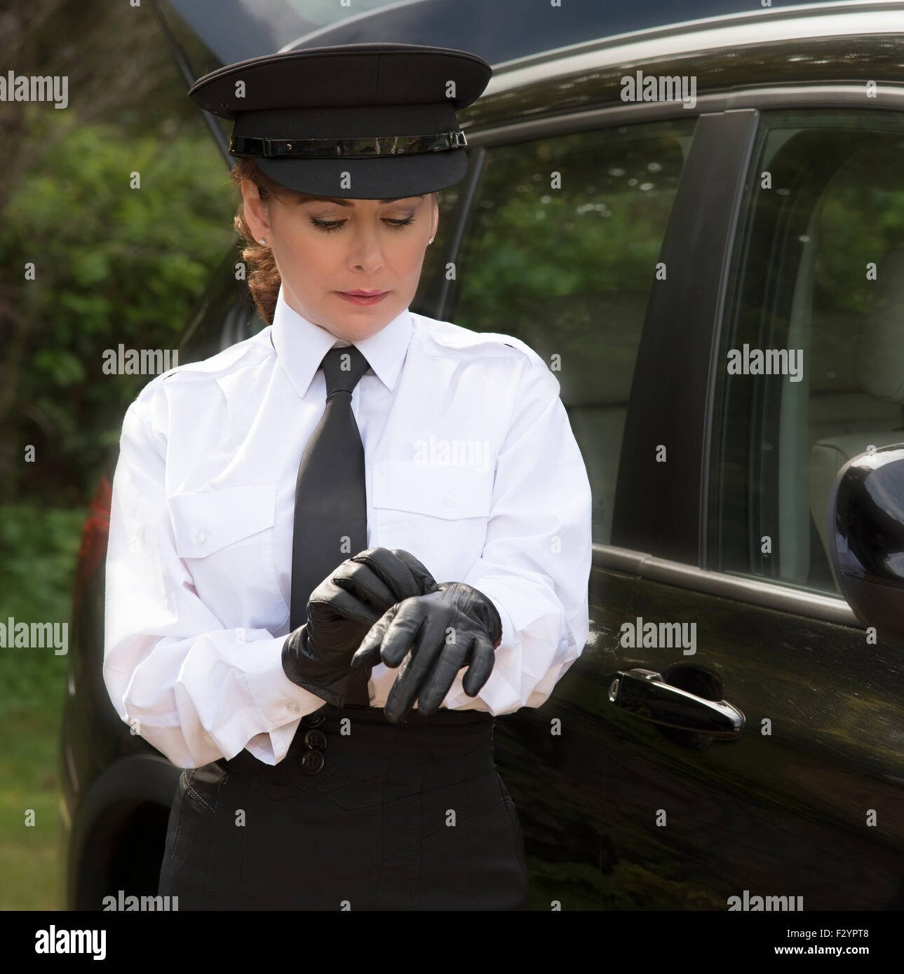 Black leather uniform gloves - Woman Chauffeur Wearing A Hat And Putting On Her Uniform Black Leather Gloves Stock Image
