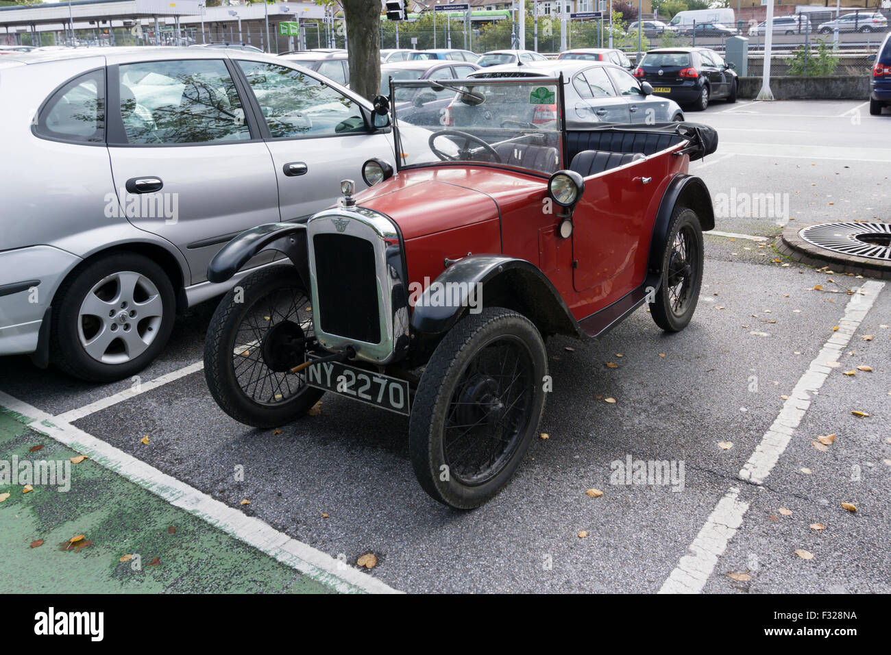A small vintage Austin 7 car in a car park with larger modern ...