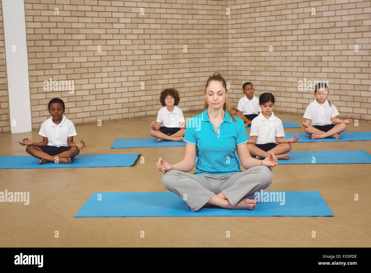 Modular Classroom Yoga ~ Students and teacher doing yoga pose stock photo royalty
