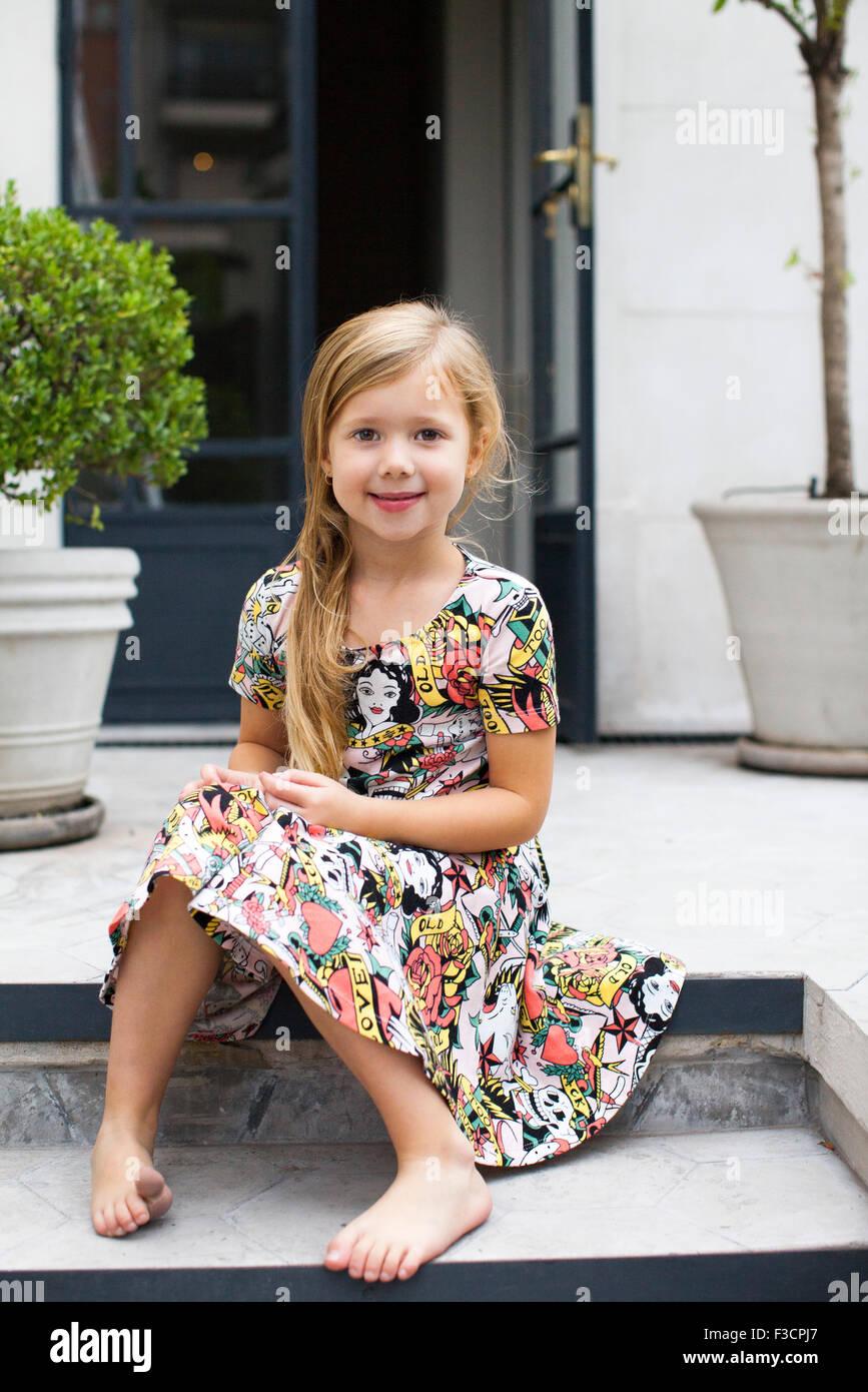 little girl sitting on steps portrait stock photo