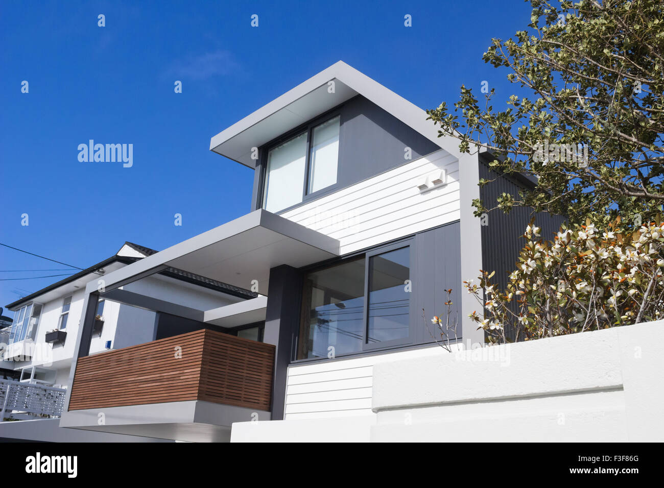 modern gray and white house with blue sky and wooden balcony and stock photo royalty free image. Black Bedroom Furniture Sets. Home Design Ideas