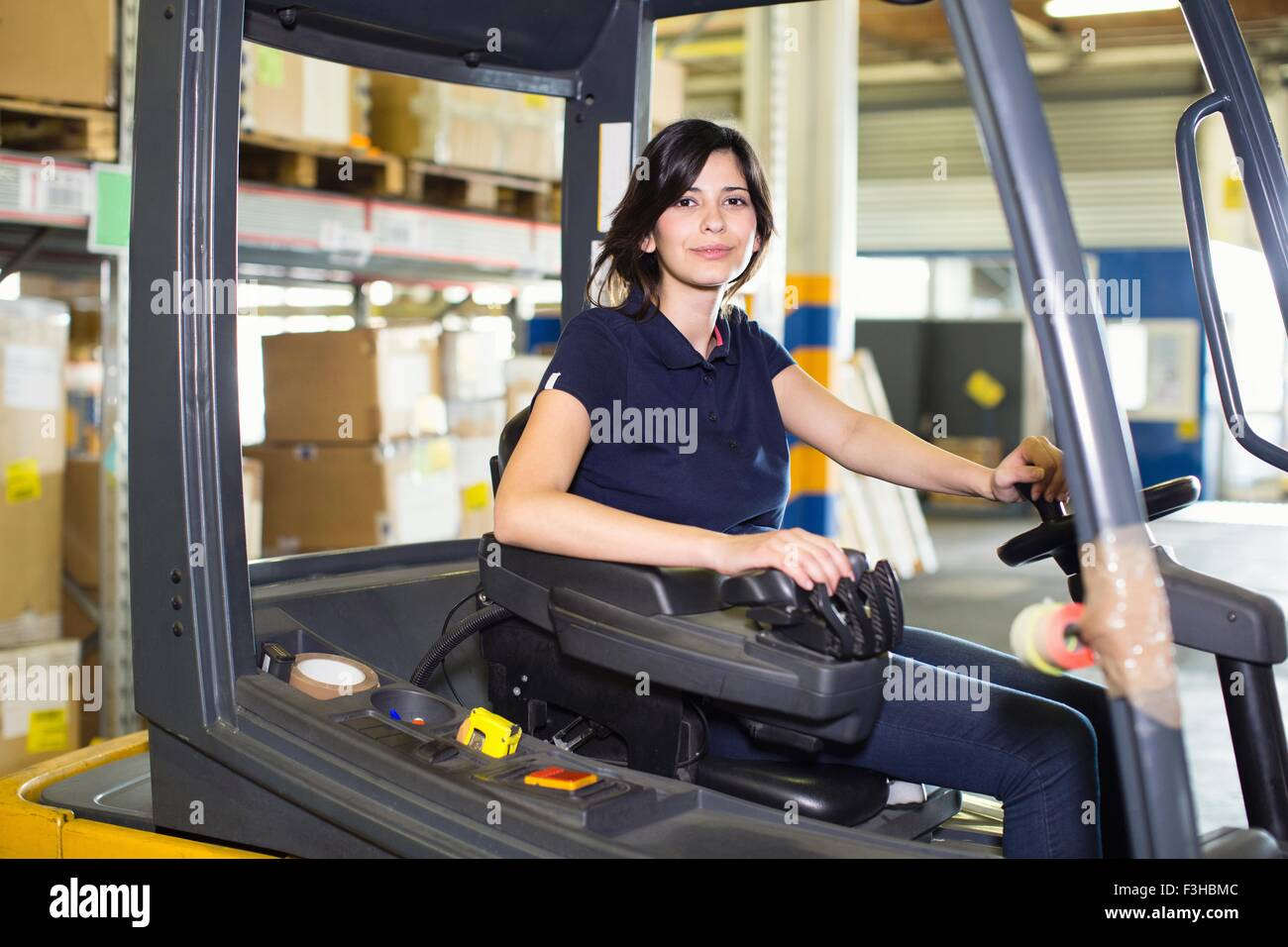 Portrait of female forklift truck driver working in distribution warehouse stock image