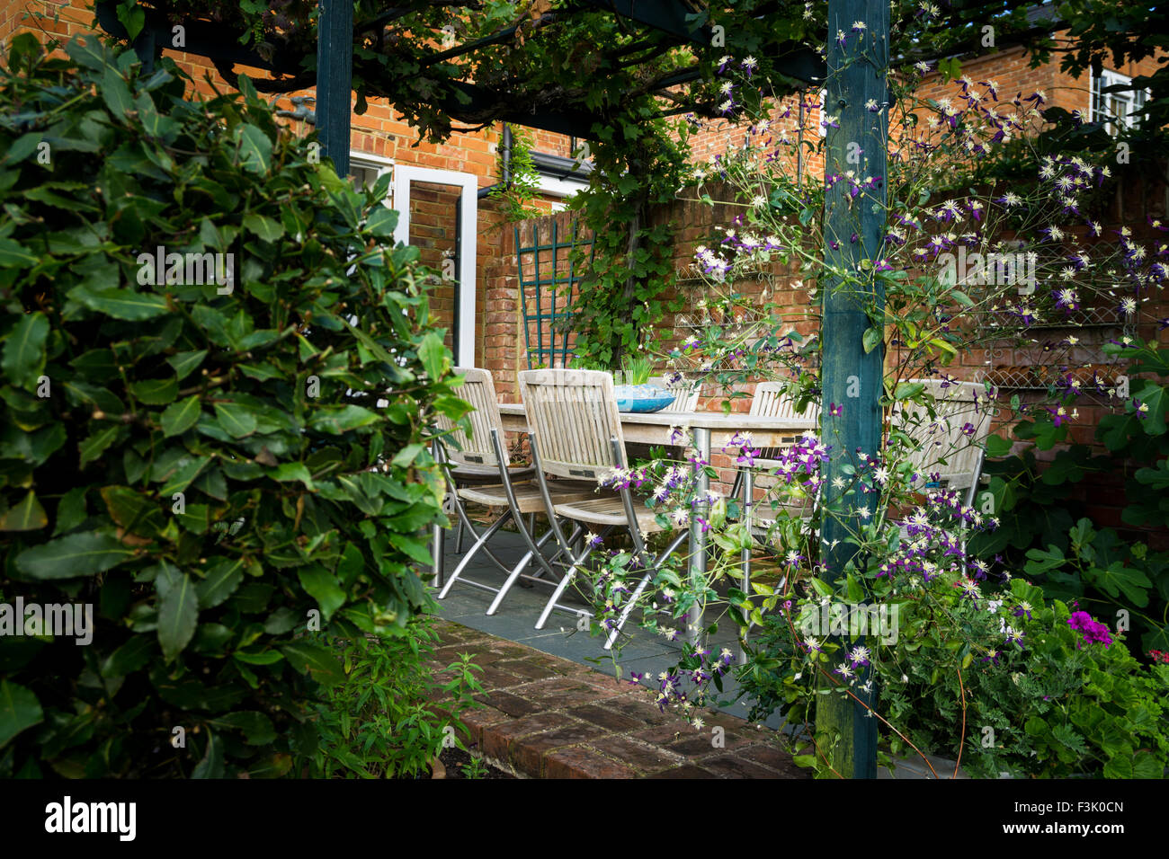 A Table And Chairs In The Shade Of A Vine Covered Pergola In An English  Country Garden.