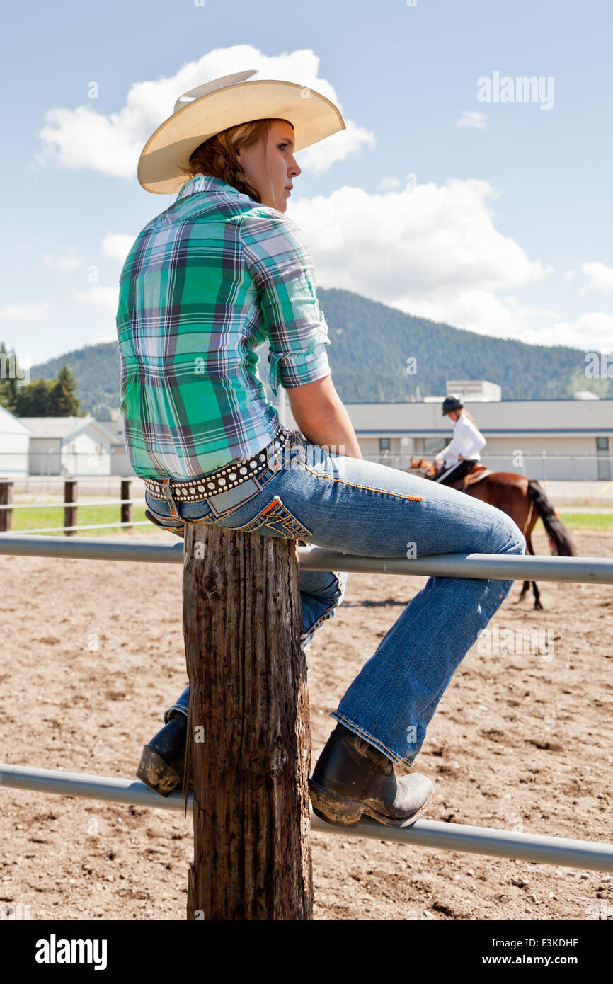 A Western Teenage Girl Sitting On A Fence At An Equestrian