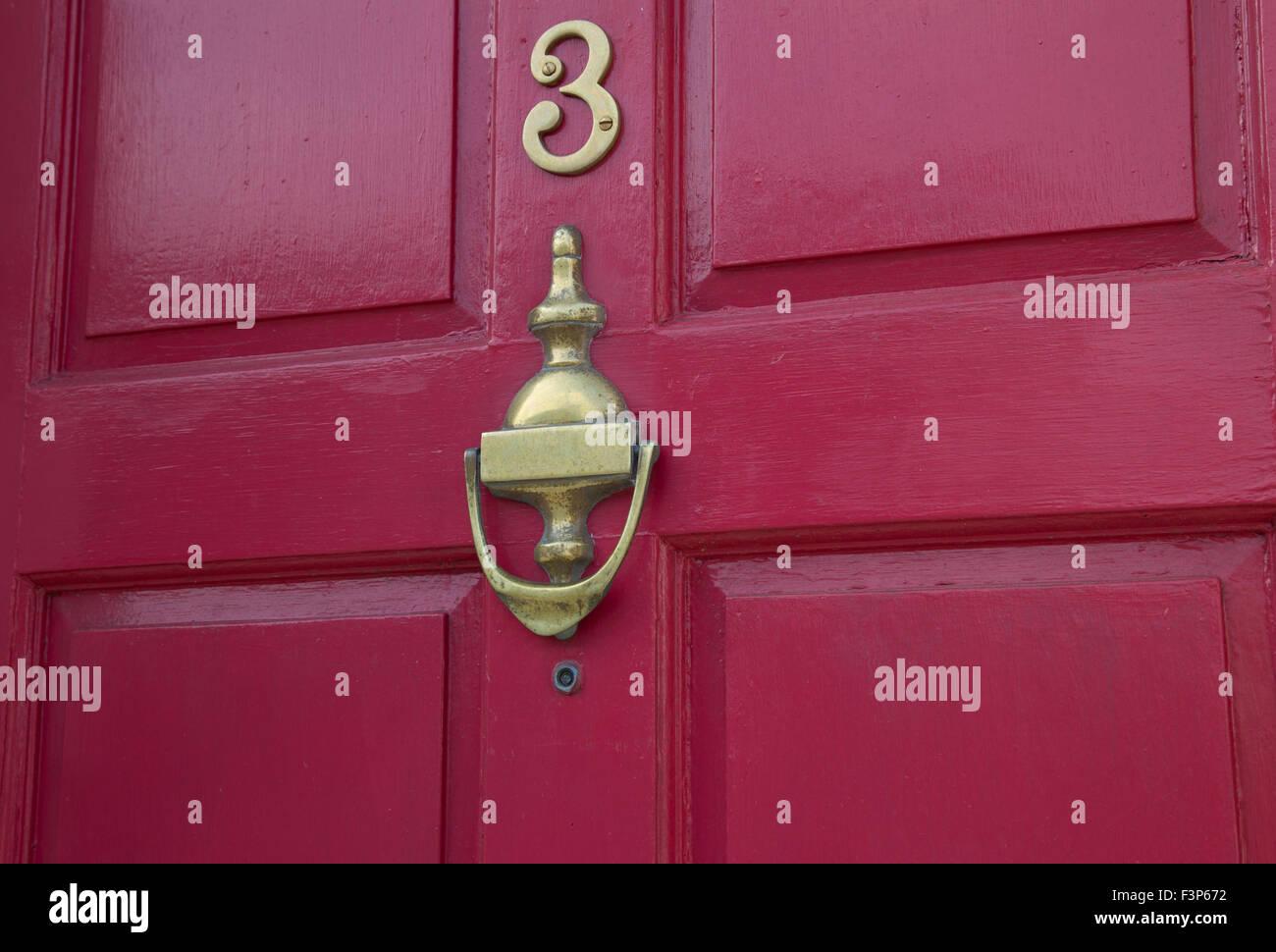 Brass Door Furniture On A Red Door
