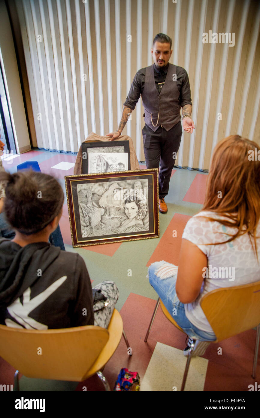 a local hispanic tattoo artist shows pictures of his work and a local hispanic tattoo artist shows pictures of his work and tells a group of multiracial teenagers a success story about his business on a careers day at