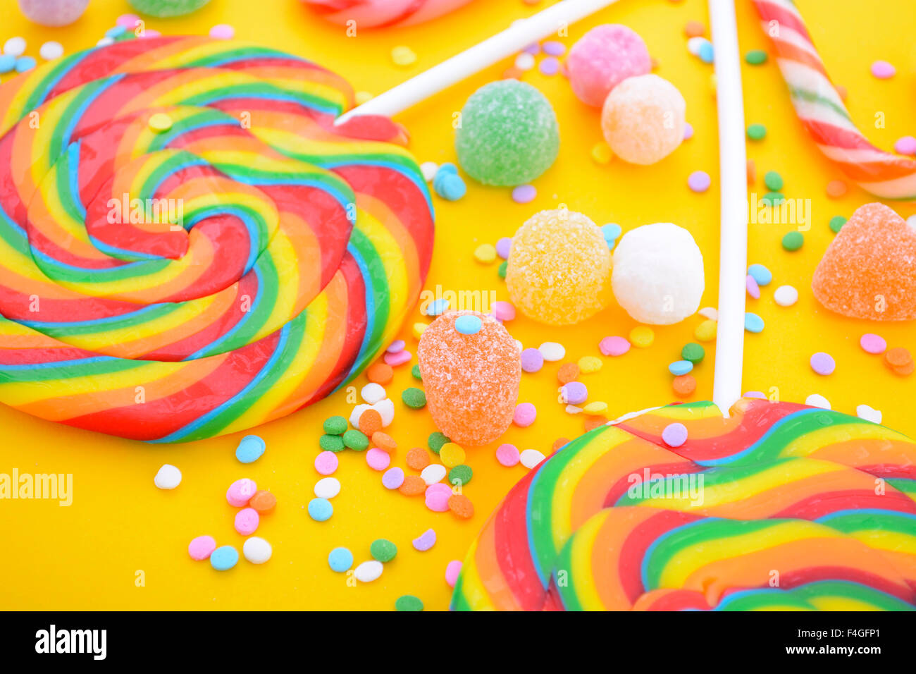 bright rainbow lollipop candy on colorful yellow wood table for halloween trick or treat or childrens party