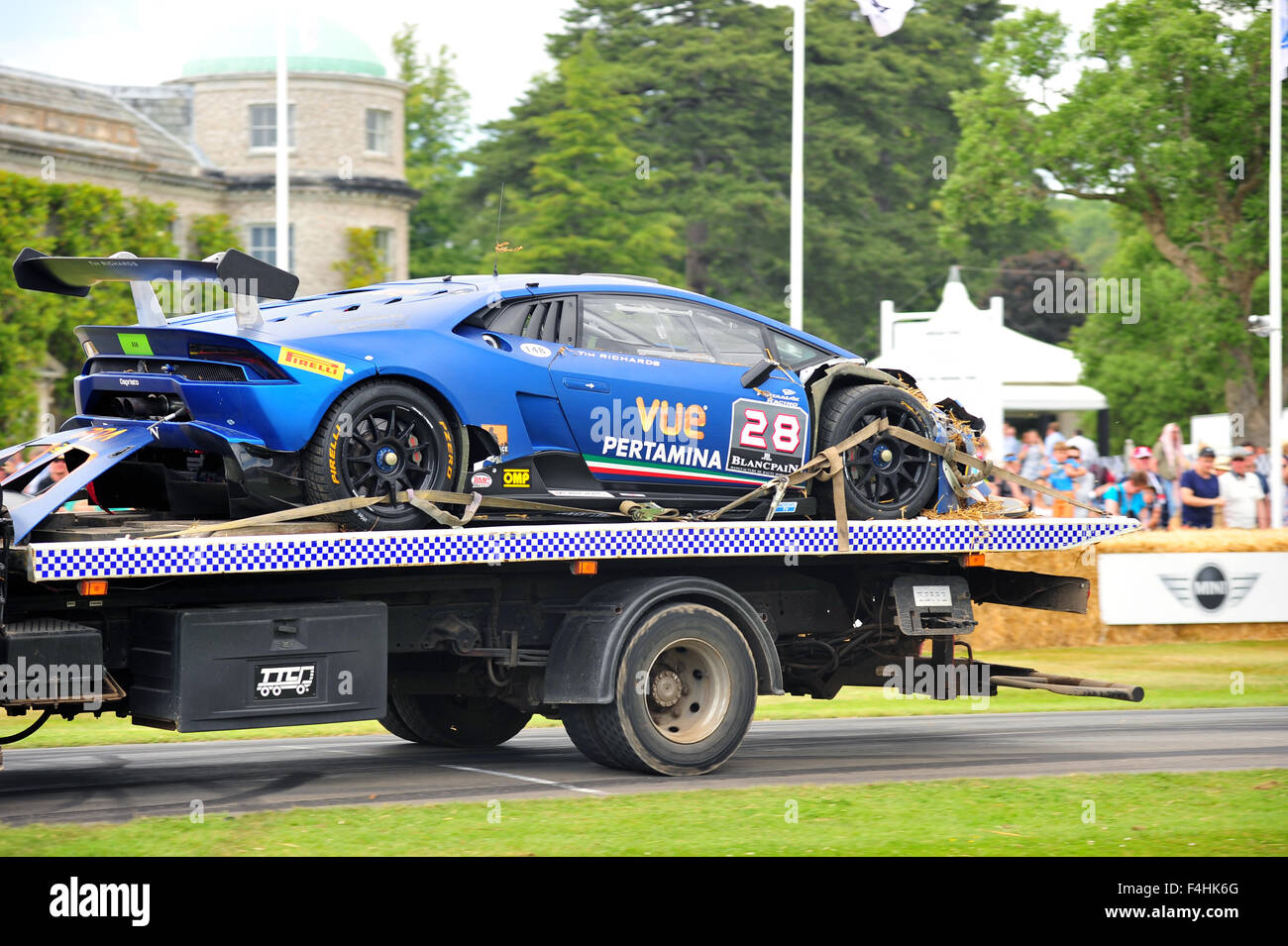A Damaged Lamborghini Huracan Super Trofeo Transported On The Back Of A  Flatbed Truck At The