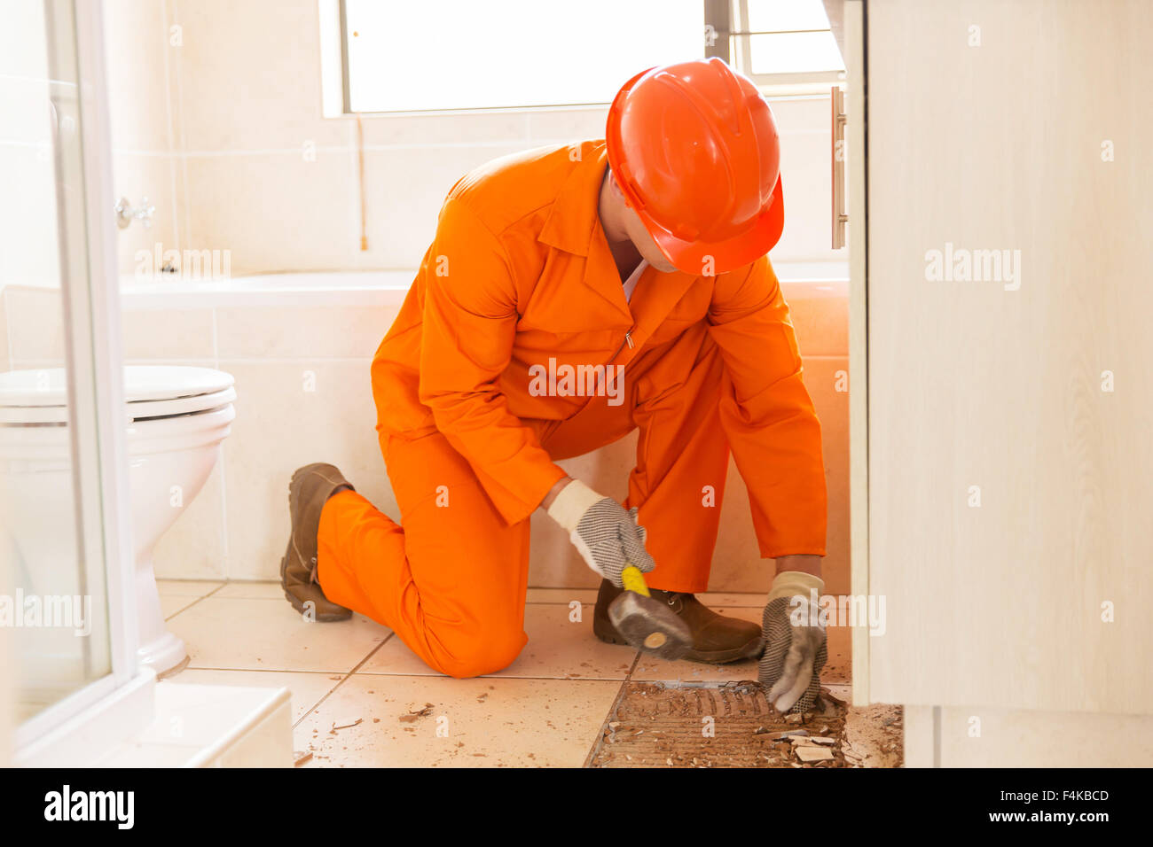 Construction worker removing old floor tiles using a hammer and construction worker removing old floor tiles using a hammer and chisel dailygadgetfo Image collections