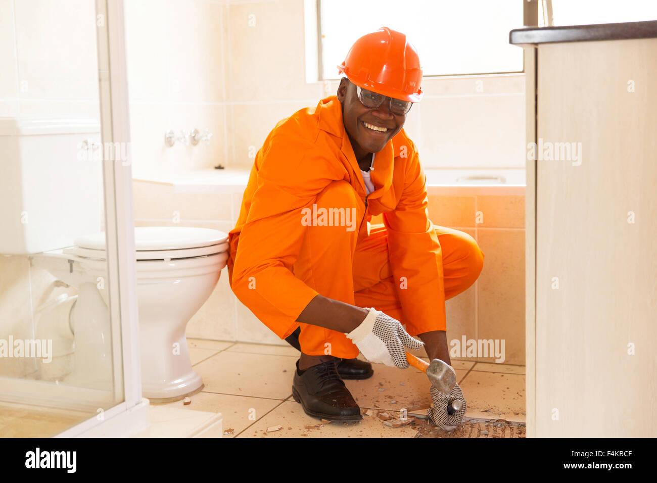 African tiles bathroom - Stock Photo Cheerful African American Construction Worker Removing Floor Tiles In Bathroom