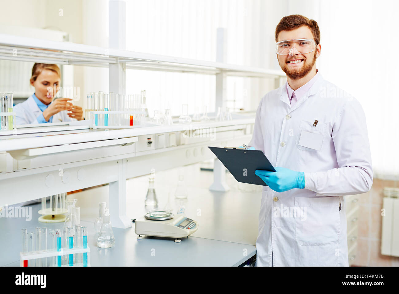 Happy chemist in white-coat, eyeglasses and gloves making notes in ...