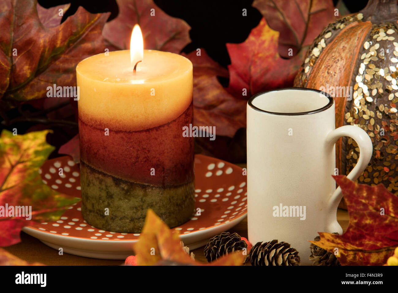 A cup of coffee with a lit candle and pumpkin decoration as a fall ...
