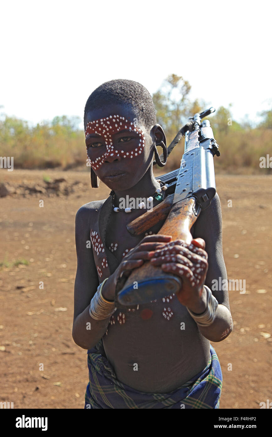 mursi Boy Stock Photo - in Maco National Park, Mursi, Mursi boy with painted face and  gun