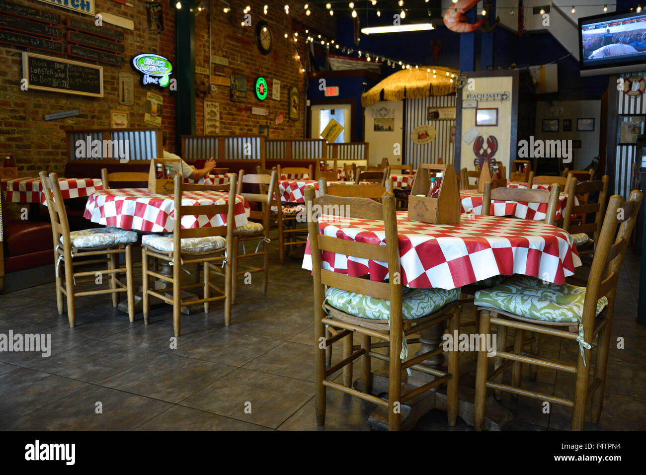 A Retro And Cool Old Historic Rustic Brick Seafood Restaurant With Menus On The Wall Fitted Red White Tablecloths