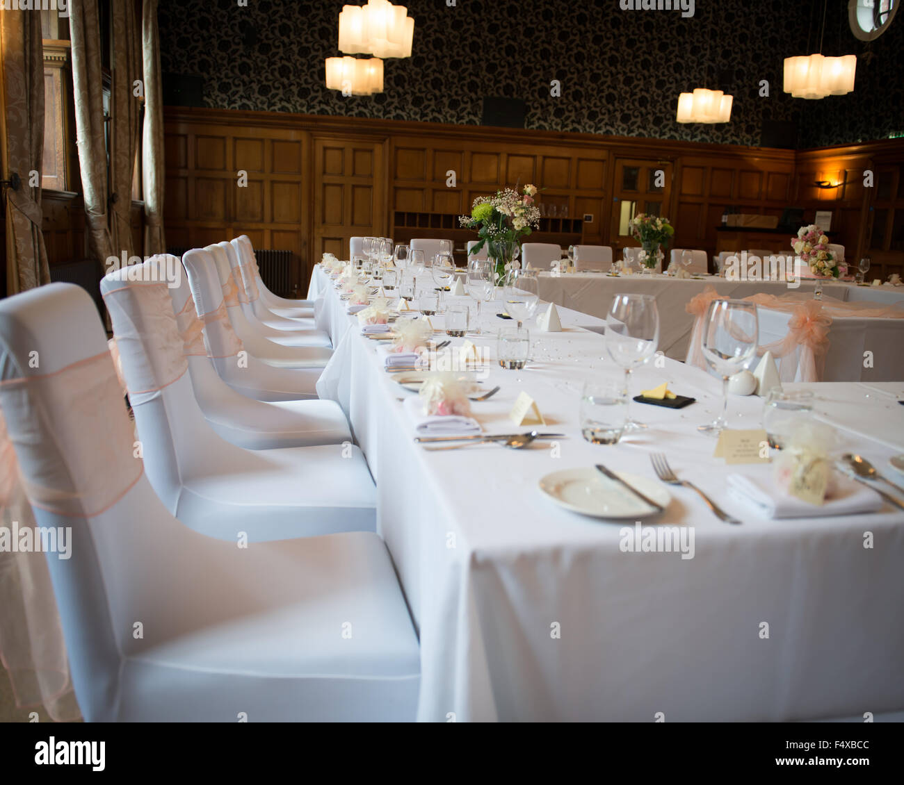Wedding Reception Table Layout Top With White Tablecloths And Peach Chair Covers Laid Silver Wear Plates Cutlery