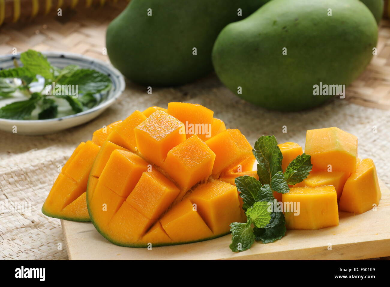 Sweet aromatic mango cut into hedgehog style and served on a small stock photo sweet aromatic mango cut into hedgehog style and served on a small wooden board garnished with mint leaves ccuart Choice Image