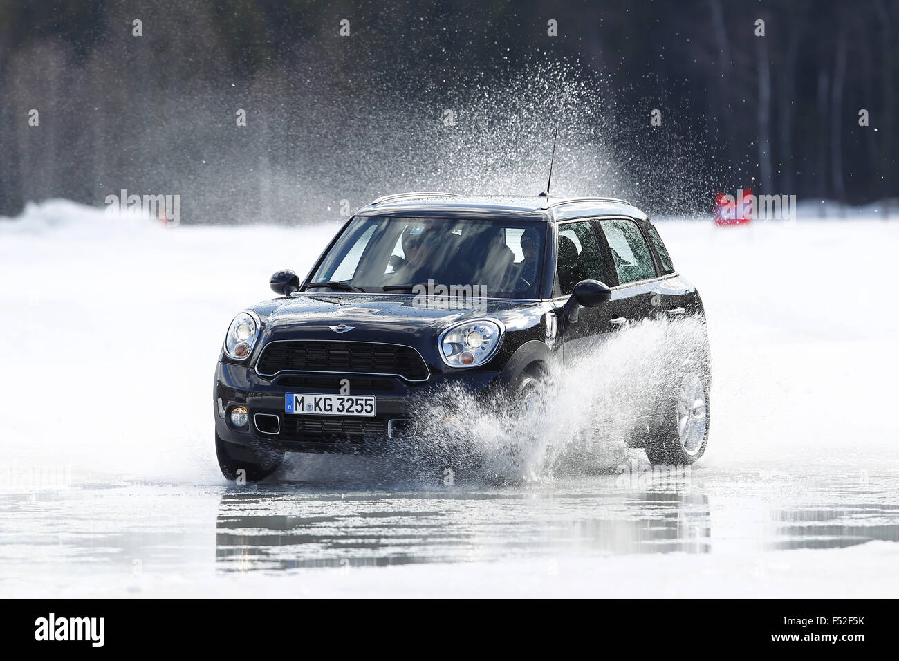 Car mini year of construction in 2012 black moving four wheel drive on ice and snow water splashes